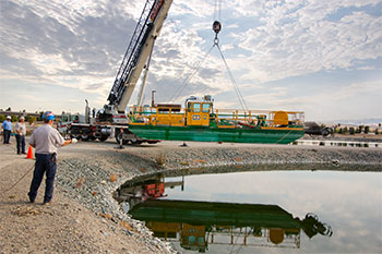 A crane lowers a dredge into a facultative sludge lagoon