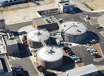 aerial view of 3 digesters and other buildings at wastewater treatment plant