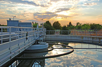 water in secondary clarifier reflects sunset