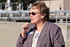woman speaking into microphone, industrial facility in background