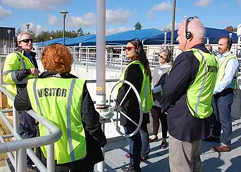 A group of people tour a water recycling plant