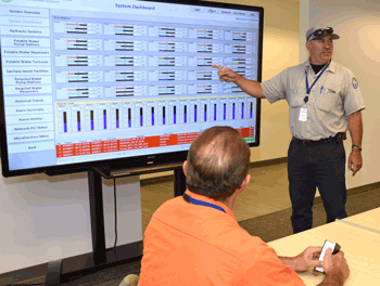 DSRSD water operator Rick Lawrence points to large video screen displaying online dashboard for DSRSD automated control systems