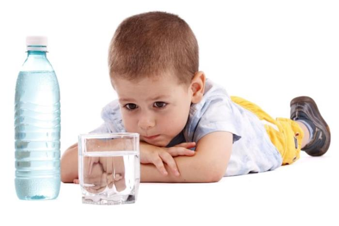 Young boy with bottle and glass of water