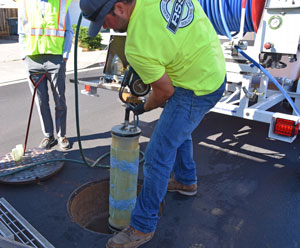 A worker lowers in the glass fiber composite into a manhole to perform a cured-in-place point repair.