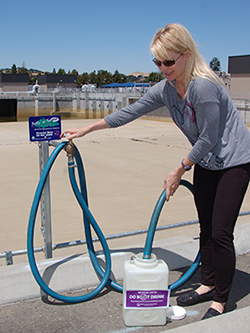 Clean Water Programs Specialist Stefanie Olson fills a container with recycled water.