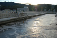 Water in an aeration basin with sun behind hills in background.