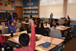 Fifth-graders raise their hands in a classroom.