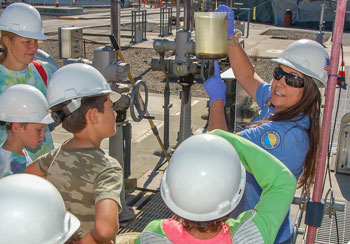 Senior Wastewater Treatment Plant Operator III Anna Garcia holds up a sample from the treatment process to a tour group of students.