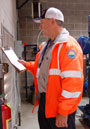 Water/Wastewater Systems Operator IV-On Call Rick Lawrence holds a clipboard at a pump station.