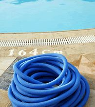 A coiled pool hose next to a swimming pool