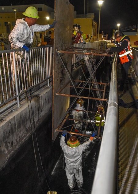 Construction crew members look into and work inside the emptied settled sewage channel during the night.