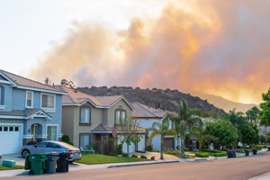 Homes with orange and gray smoke in the background.