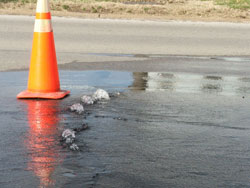 Orange cone marks water flowing from leak under a street