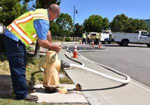 A water operator opens a hydrant to flush a drinking water main.