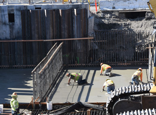 Construction workers smooth out freshly poured concrete for the base of the two new primary sedimentation tanks.